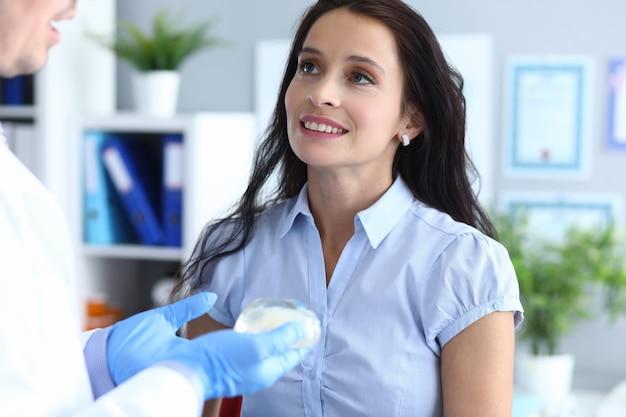 Mulher em consulta com cirurgião plástico, segurando o implante lado a lado na mão
