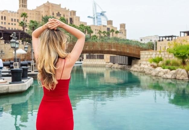 Mulher em dubai, united arab emirates. senhora atrativa que veste um vestido vermelho menina, admirar, a, cidade, vistas