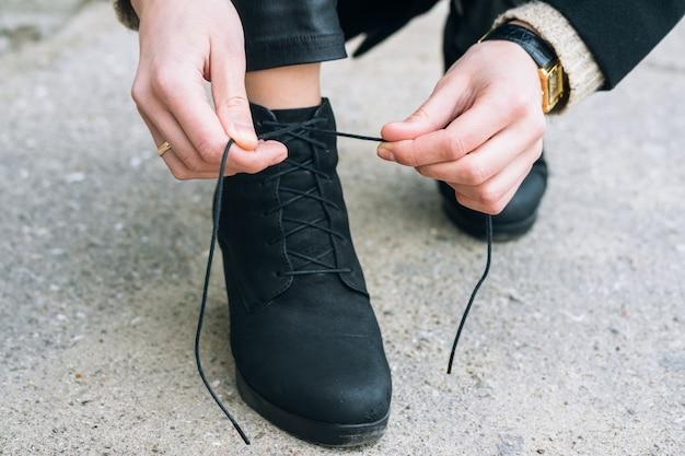 Mulher, em, elegante, roupas, amarrando, cadarços, ligado, sapatos, cima