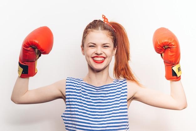 Mulher em emoções de luva de boxe vermelha de camiseta listrada.