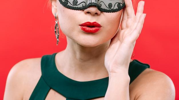 Mulher, em, escuro, máscara carnaval, soprando beijo
