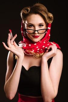 Mulher em estilo retro, posando com um batom vermelho sobre o fundo preto. retrato de pin-up