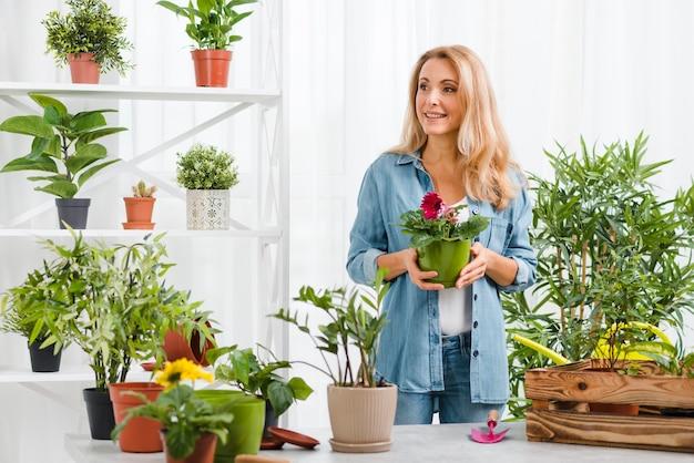 Mulher em estufa segurando o vaso de flores