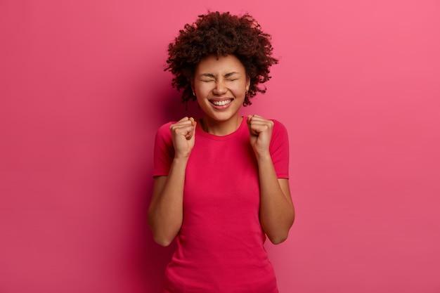 Mulher em êxtase alegre dá um soco em punho, fica muito feliz, alegra sucesso e triunfo, festeja muito dinheiro na loteria, fecha os olhos, veste roupas rosa, posa em casa vitória realizada