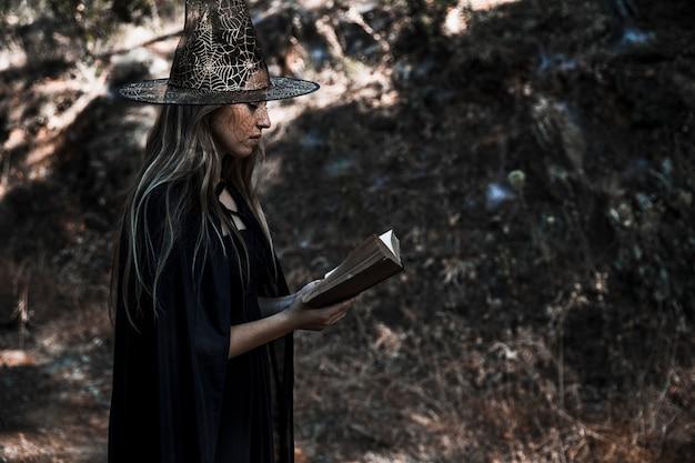 Mulher, em, fantasia bruxa, livro leitura