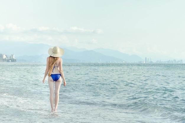 Mulher em fato de banho e chapéu caminha à beira-mar. vista de trás