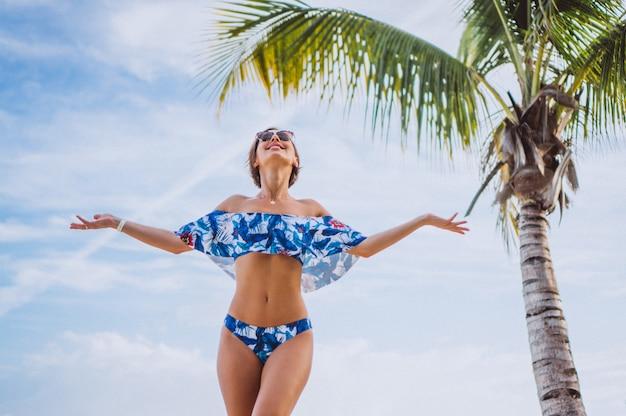Mulher em fato de banho em pé na praia perto da palma da mão