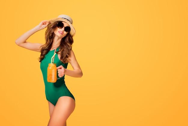 Mulher em fato de banho segurando bebida