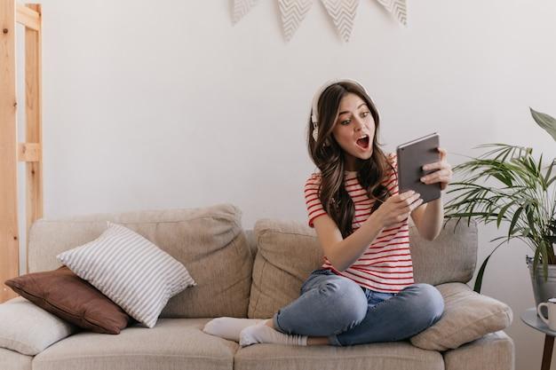Mulher em fones de ouvido enormes emocionalmente e surpresa olha para a tela do tablet