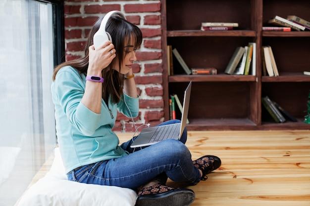 Mulher em fones de ouvido está trabalhando em um laptop