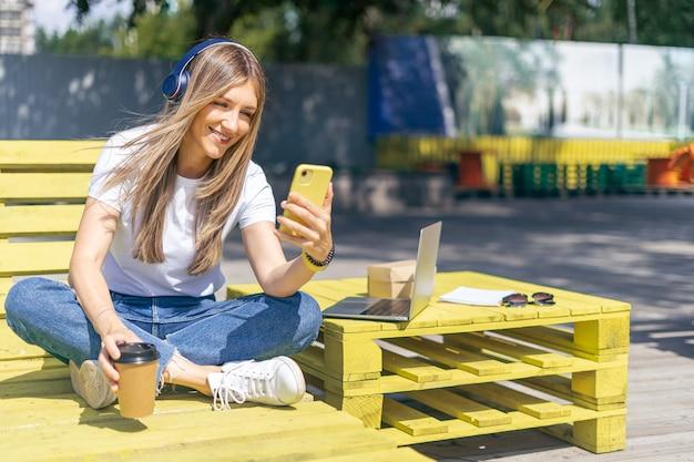 Mulher em fones de ouvido, tendo uma chamada de vídeo. garota feliz e sorridente trabalhando fora e tomando café