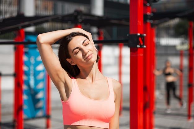 Mulher em forma com roupa esportiva rosa se esticando ao ar livre