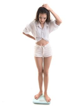 Mulher em forma de garota fitness comemorando o sucesso na escala de peso em branco