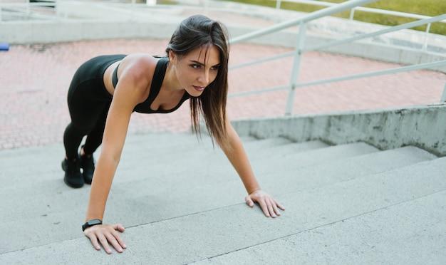 Mulher em forma de jovem fazendo exercícios de flexão em escadas ao ar livre em um ambiente urbano