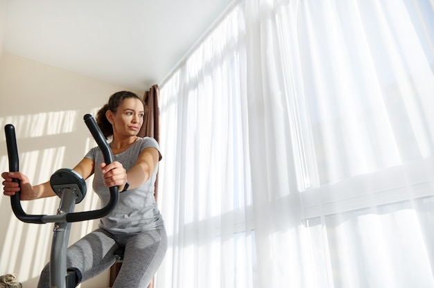 Mulher em forma de jovem usando bicicleta ergométrica para exercícios aeróbicos em casa