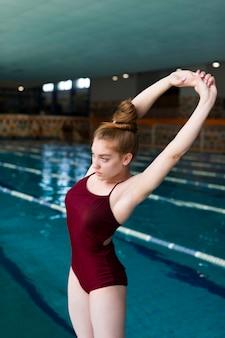 Mulher em forma de tiro médio se alongando perto da piscina