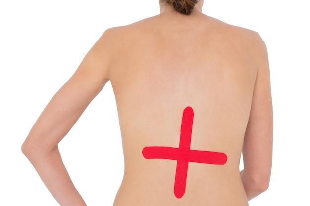 Mulher em forma de topless com sinal de cruz vermelha na parte de trás
