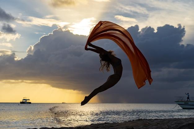 Mulher em forma flexível pulando com seda durante o pôr do sol dramático com nuvens tempestuosas