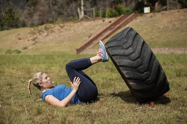 Mulher em forma realizando treino de perna com nível durante a pista de obstáculos no campo de treinamento