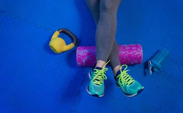 Mulher em forma usando um rolo de espuma na perna para liberar a tensão e ajudar com dores musculares após o treino na academia