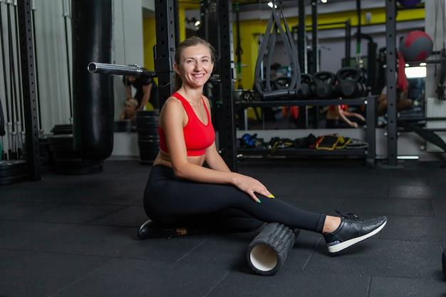 Mulher em forma usando um rolo de espuma para aliviar os músculos doloridos após um treino em uma academia moderna