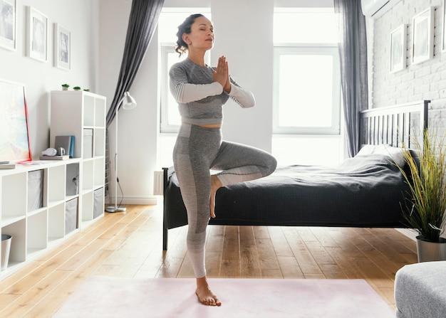 Mulher em foto completa em pé sobre uma perna