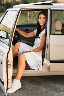 Mulher em foto completa posando no carro