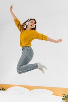 Mulher em foto completa pulando com fones de ouvido