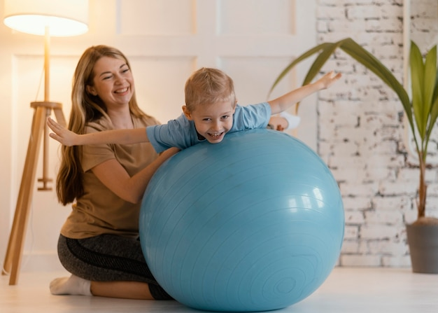 Mulher em foto completa segurando a criança na bola de ginástica