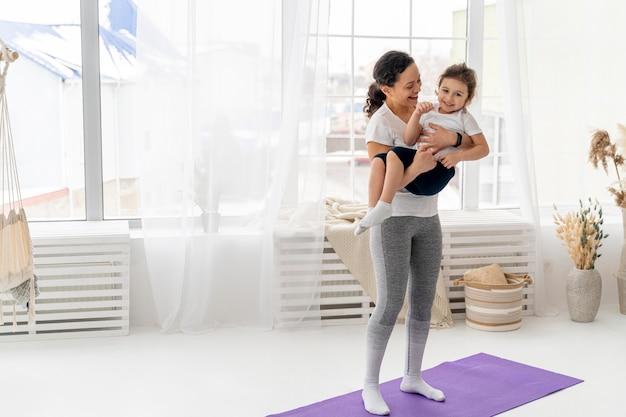 Mulher em foto completa segurando criança nos braços