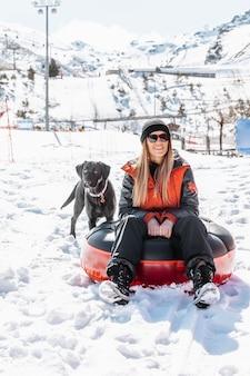 Mulher em foto completa sentada ao ar livre com um cachorro