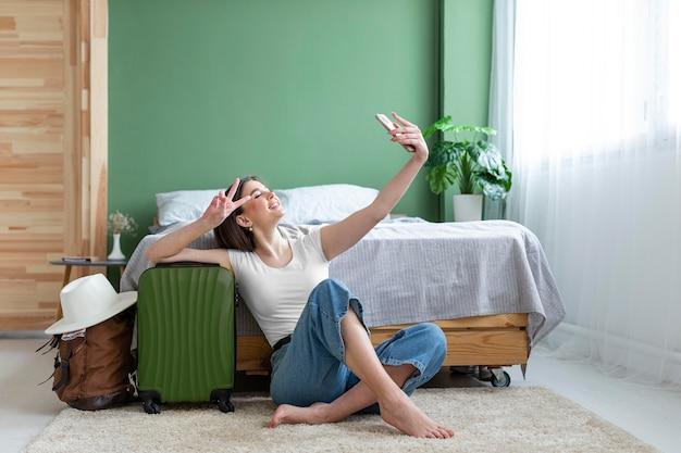 Mulher em foto completa tirando selfie com a bagagem