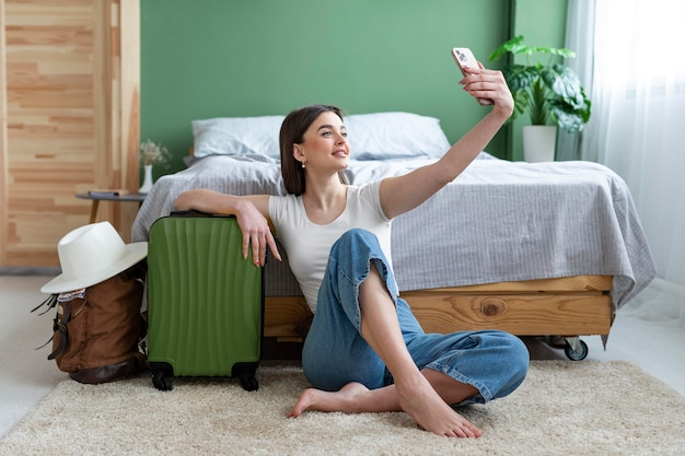 Mulher em foto completa tirando selfie em casa