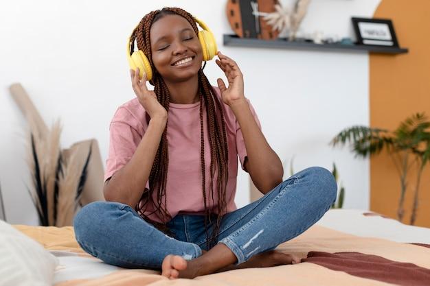 Mulher em foto completa usando fones de ouvido amarelos