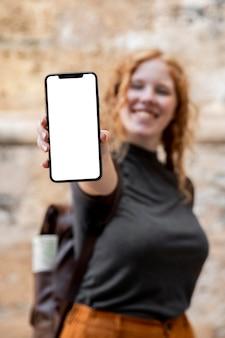 Mulher em foto mostrando um telefone em branco