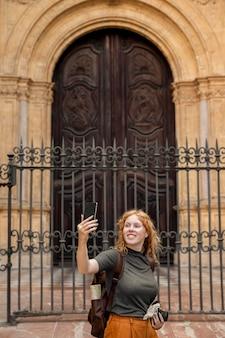 Mulher em foto tirando selfie em frente ao prédio