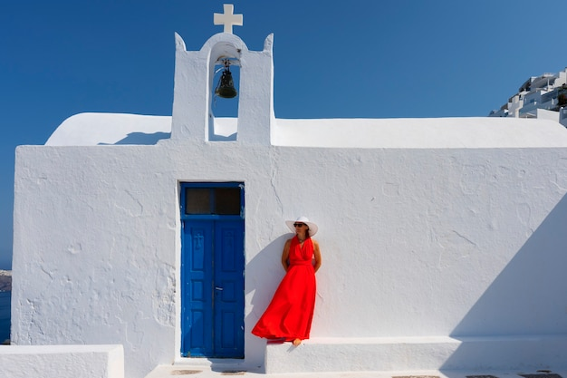 Mulher em frente à igreja em santorini, grécia