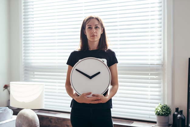 Mulher em frente à mesa e segura um relógio.