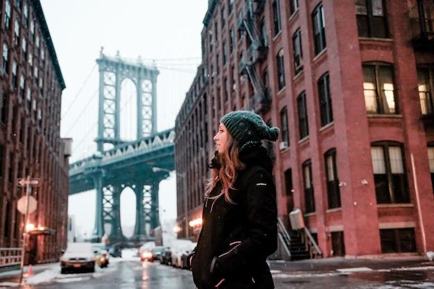 Mulher em frente à ponte de manhattan em nova york no inverno com um chapéu azul