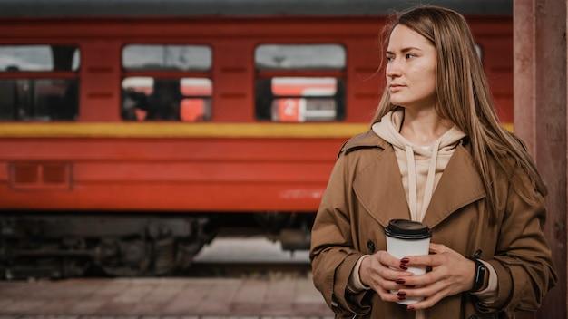 Mulher em frente a um trem na estação ferroviária