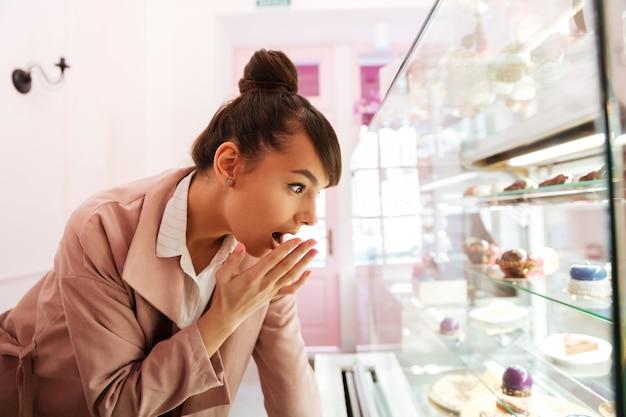 Mulher em frente a vitrine de vidro com bolos dentro de casa