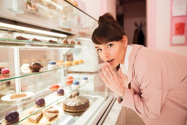 Mulher em frente a vitrine de vidro com bolos