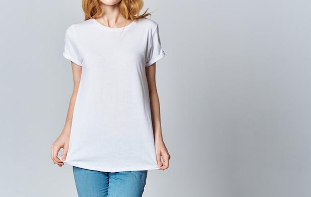 Mulher em gestos de t-shirt e jeans branca com as mãos cortadas vista do modelo.
