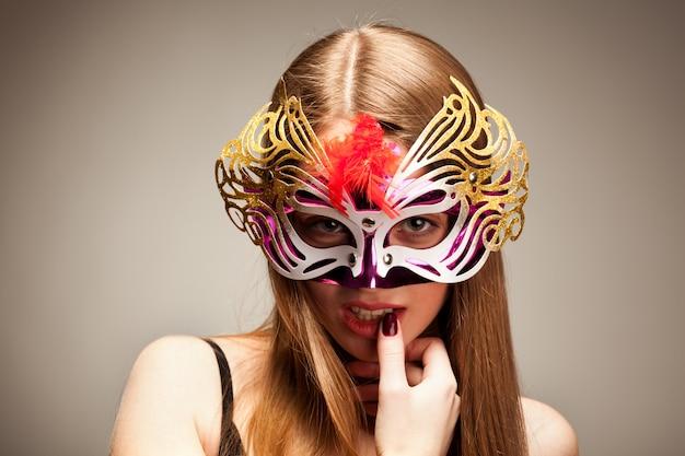 Mulher em grande máscara de carnaval multicolorida