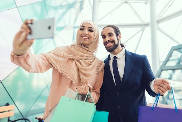 Mulher em hijab fazer selfie no shopping.