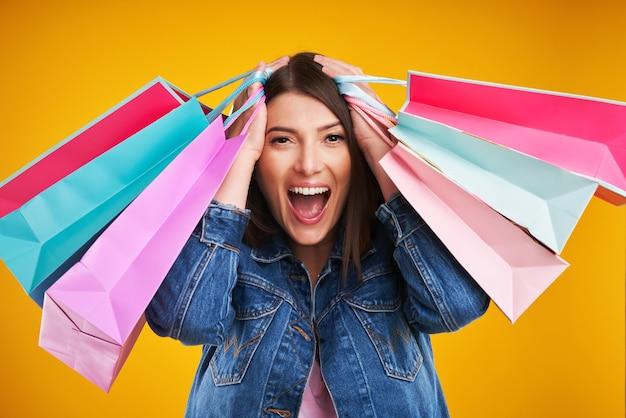 Mulher em jaqueta jeans com sacolas de compras sobre fundo amarelo