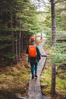 Mulher em jeans azul e mochila laranja caminhando na ponte de madeira
