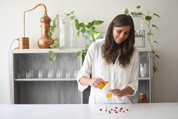 Mulher em laboratório de cosmética trabalhando com óleos essenciais