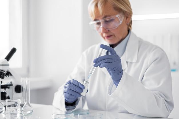 Mulher em laboratório fazendo experimentos