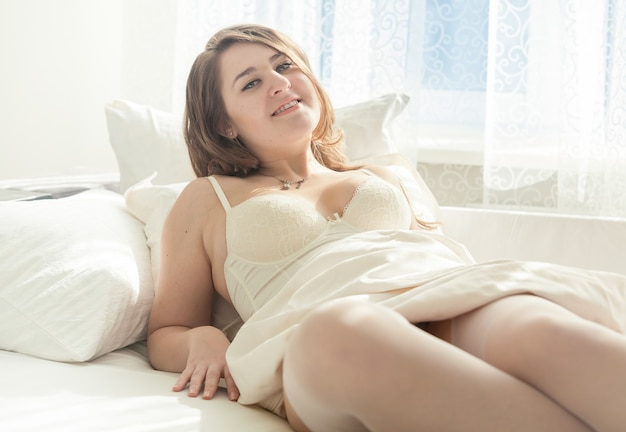 Mulher em lingerie branca acordando na cama